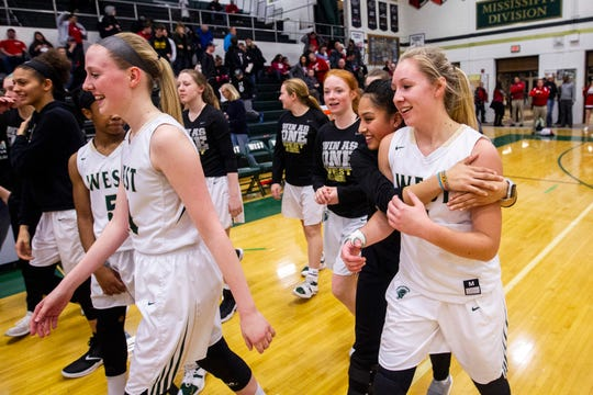 Iowa City West's Lauren Zacharias, far right, celebrates with teammates after a Class 5A girls' basketball game on Thursday, Jan. 31, 2019, at West High School in Iowa City, Iowa. The Women of Troy defeated the City High Little Hawks, 65-51.