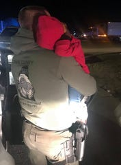 A Rankin County deputy holds a two-year-old girl that was with a man and a woman who were the targets of a drug bust.