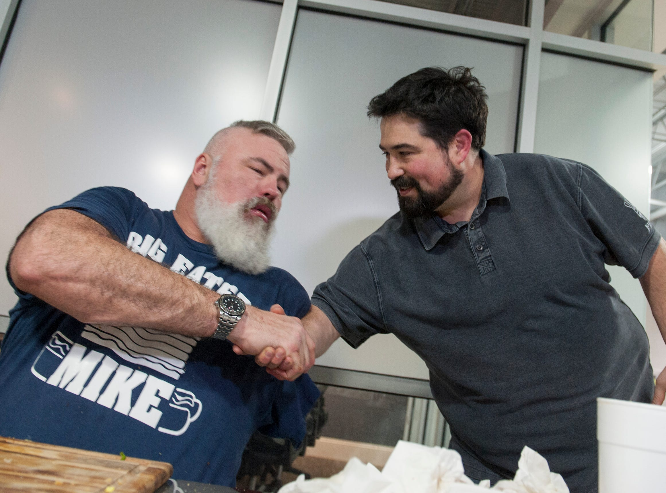 Mike Whities of Brandon, also known as Big Eater Mike, celebrates winning Roosters' first Stupid Burger Challenge Friday, Feb. 1, 2019, with Rooster's owner Nathan Glenn. Big Eater Mike tackled a 6-pound, 8-ounce platter of burger and fries within 30 minutes at the Fondren restaurant.