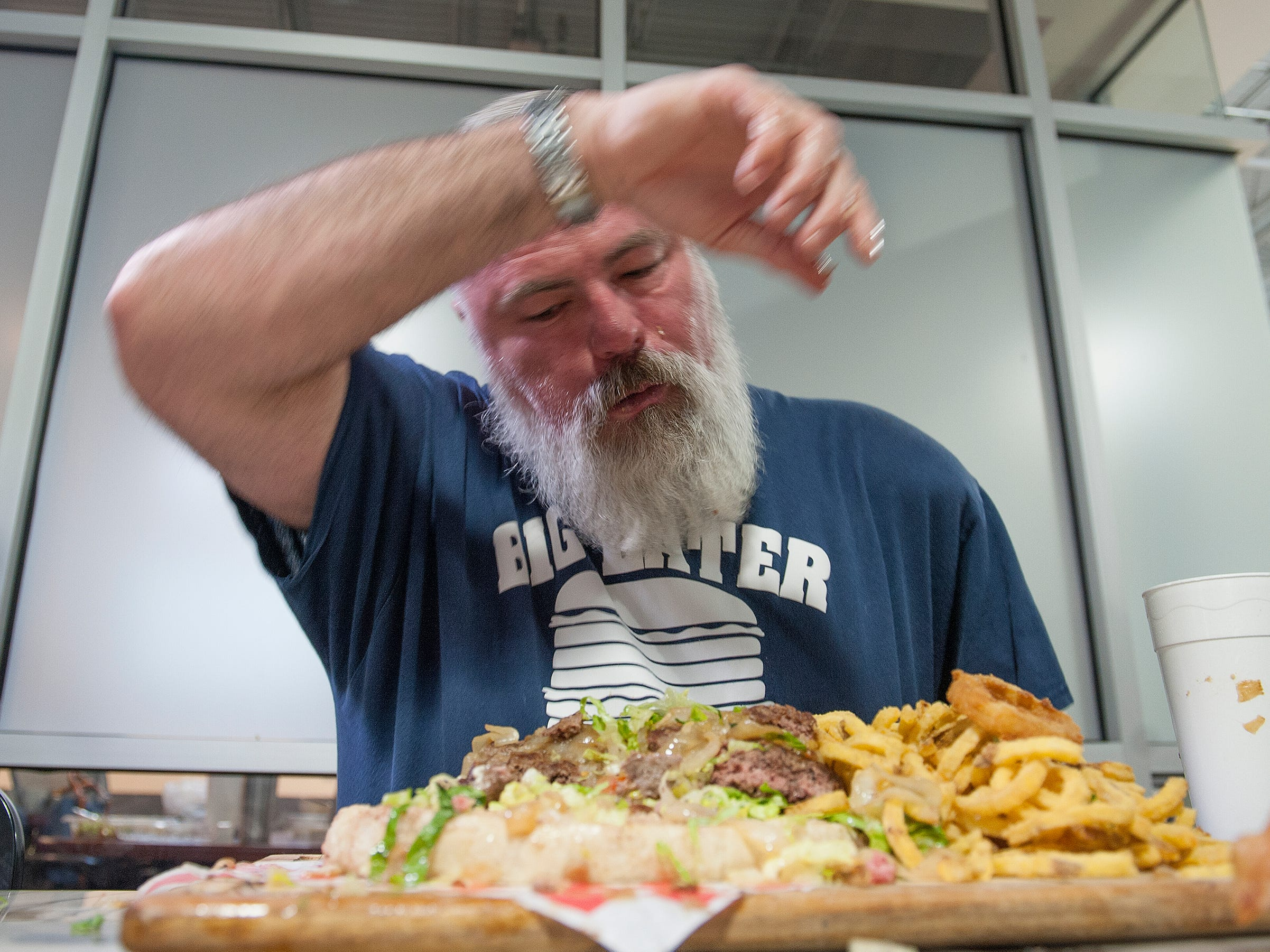 Big Eater Mike feels the strain as he pauses to wipe sweat off his brow during Rooster's Stupid Burger Challenge Friday, 1, 2019, in the Fondren district of Jackson.