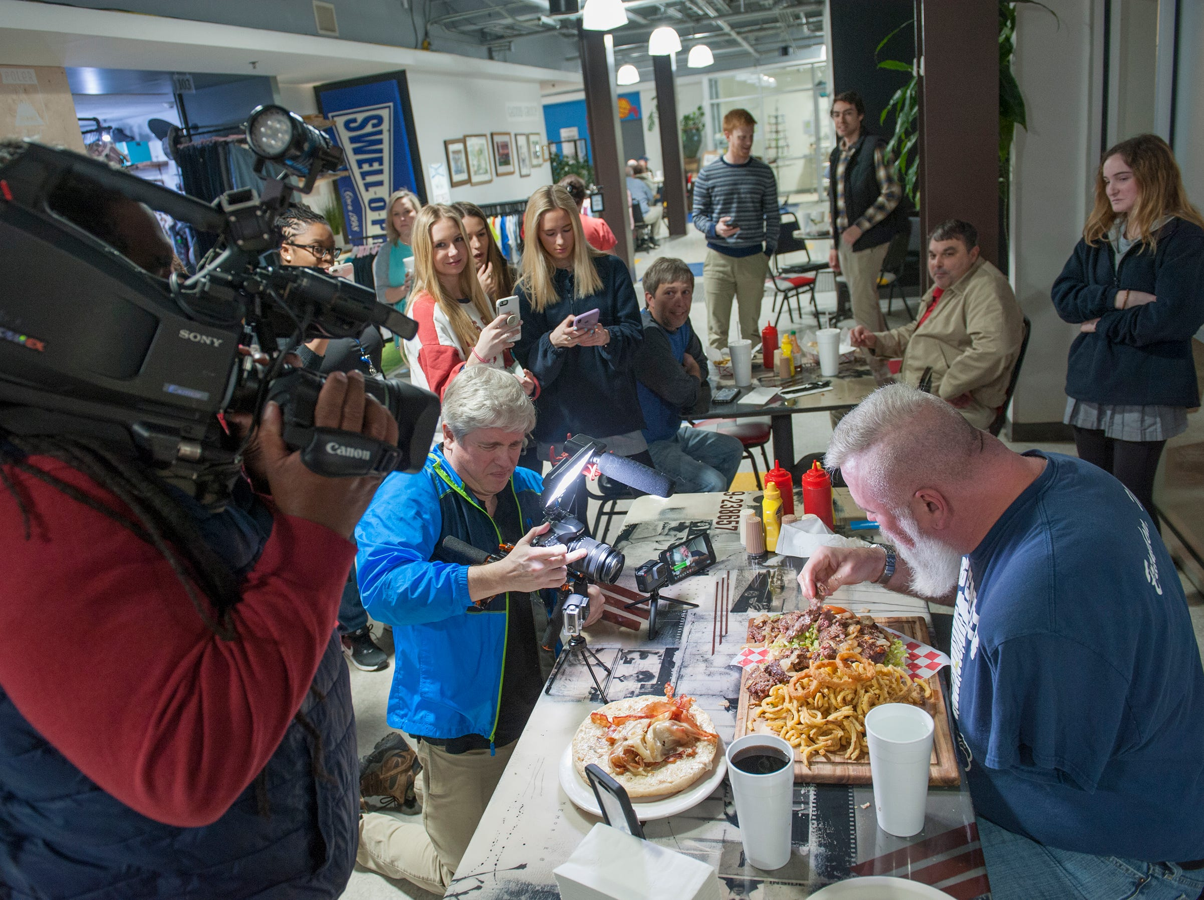 A crowd gathers to witness Mike Whities of Brandon, also known as Big Eater Mike, tackled a 6-pound, 8-ounce platter of burger and fries within 30 minutes during the Roosters' Stupid Burger Challenge Friday, Feb. 1, 2019 at the Fondren restaurant.