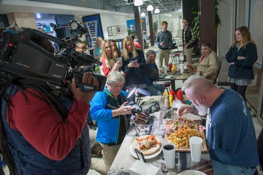 A crowd gathers to witness Big Eater Mike, tackled a 6-pound, 8-ounce platter of burger and fries within 30 minutes.