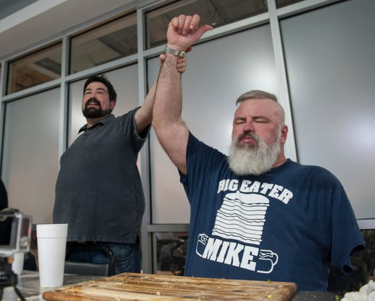 Big Eater Mike celebrates winning the Stupid Burger Challenge with Rooster's owner Nathan Glenn, right.