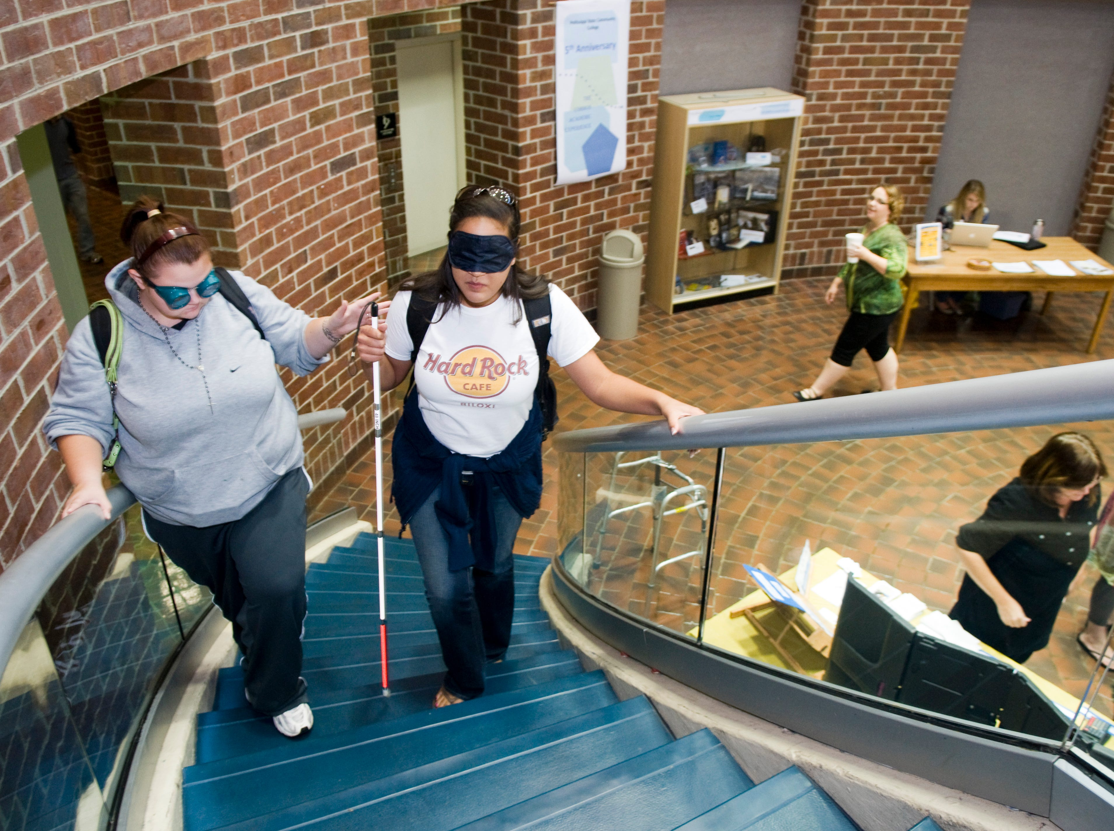 Students Victoria Love, left, and Tiffany Simpson take part in the 'Walk a Mile in My Shoes' disability awareness program Thursday, Oct. 21, 2010 at Pellissippi State Community College. Students, faculty, staff and community members were invited to 'try on' a disability and go about the routine of work and school as part of National Disability Employment Awareness Month.