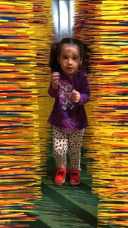 "2-year-old Carmela Gosnell enjoys the sculpture in its current home at the Muse, where child visitors have nicknamed it ""the Carwash."""