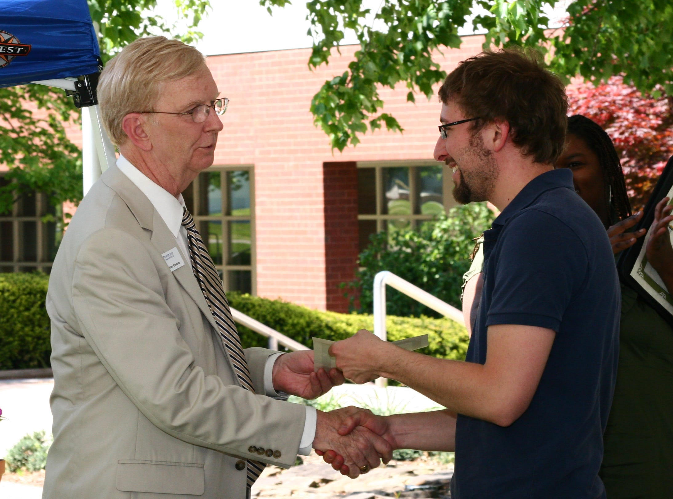Pellissippi State Community College President Allen Edwards congratulates student Steven McLaurin on his achievements with Student Activities April 30, 2010.