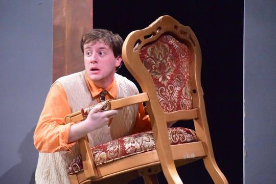 "Brindsley Miller (Jackson Burnette) tries to remove stolen furniture completely in the dark during ""Black Comedy""."