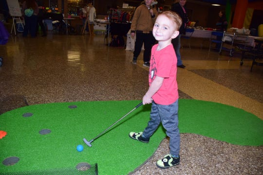 Nash Leopper, 3, plays a putt-putt game in the Kids Zone during the Community Winter Bazaar held at Karns High School Saturday, Jan. 26.