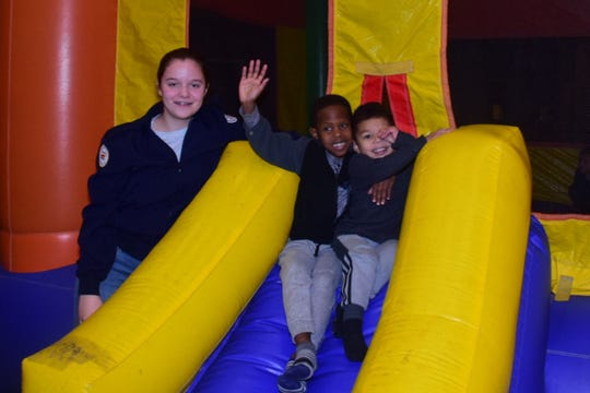 Laura Vogel, 14., a JrROTC Cadet, gives Braylon Lowrance, 5, and Bemas McCoy 3, a helping hand on an inflatable slide during the Community Winter Bazaar held at Karns High School Saturday, Jan. 26.
