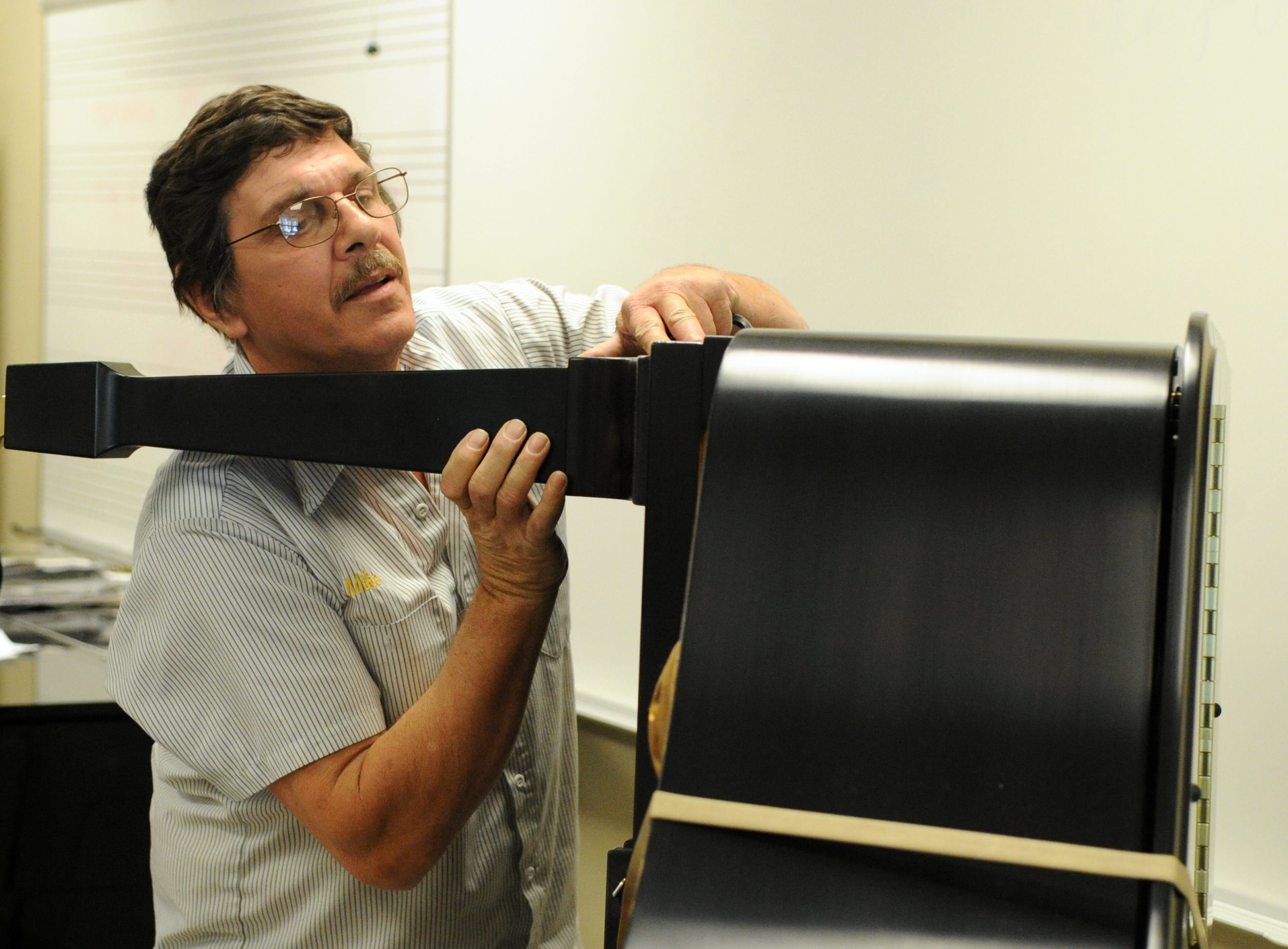 Mike Dheohary attaches the leg to a Steinway grand piano at Pellissippi State Community College Thursday, May 5, 2011.  Dheohary works with the American Piano Gallery and helped deliver 10 Steinway pianos to the college as a part of their all-Steinway status.