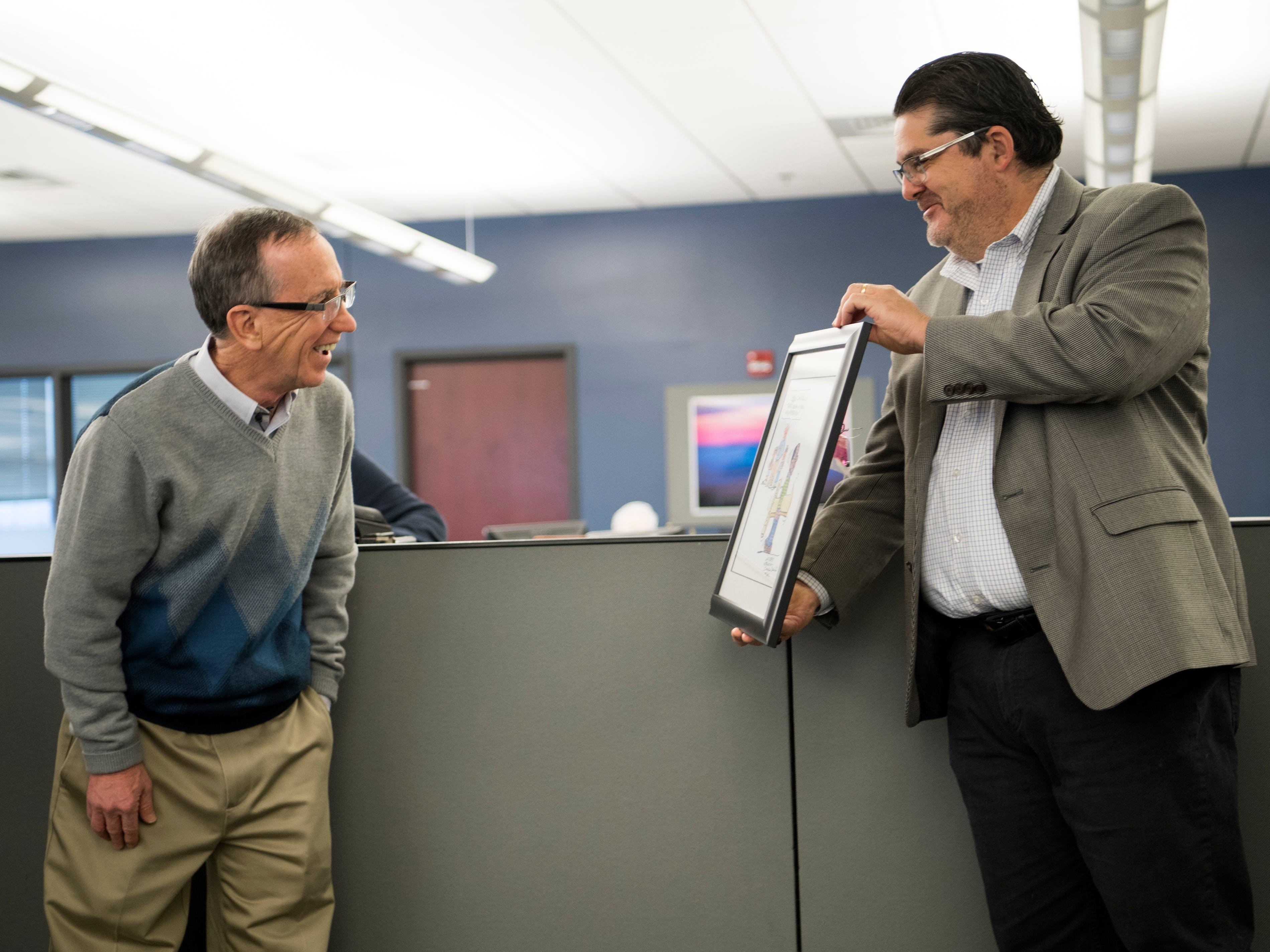 Michael Anastasi, Vice President/News for USA TODAY NETWORK Tennessee, shows executive editor Jack McElroy the custom Charlie Daniel cartoon made for McElroy during a celebration for the retirements of executive editor Jack McElroy and cartoonist Charlie Daniel in the News Sentinel newsroom on Friday, February 1, 2019.