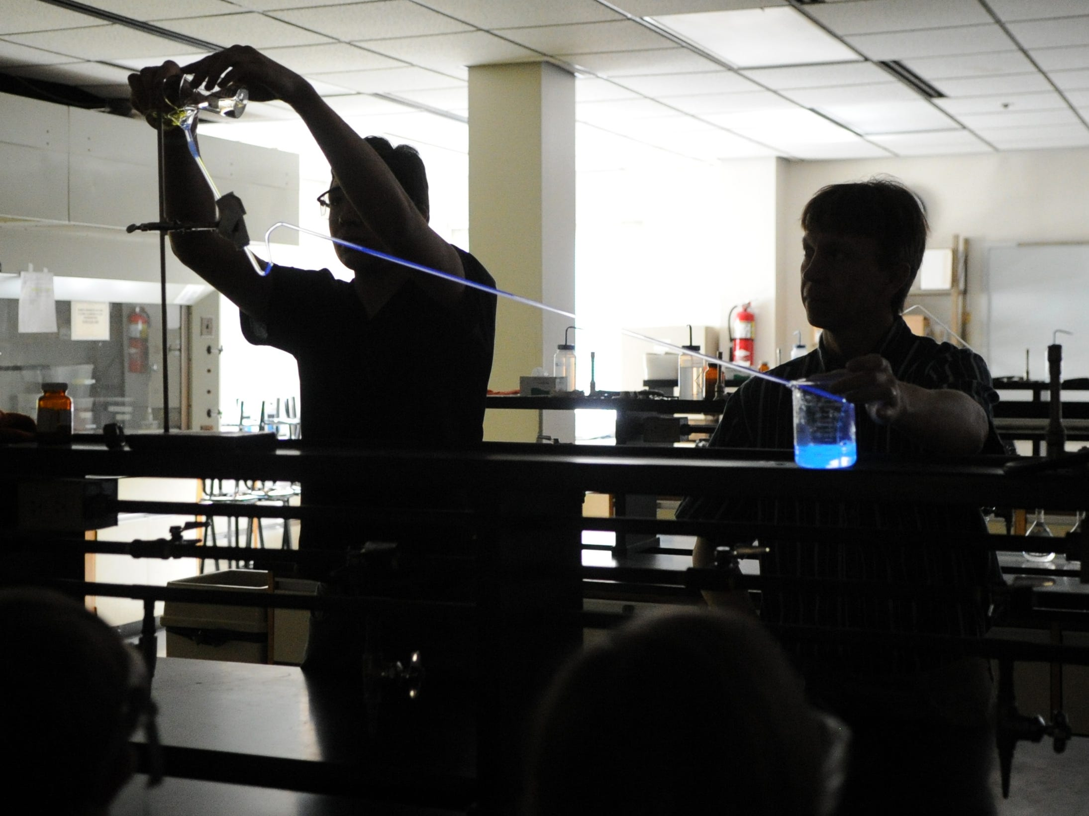 Matthew Donahue, left, and Dr. Terry Burns, right, perform an experiment that simulates the chemical reaction that occurs in lightning bugs during the Young Inventors Fair at Pellissippi State Community College Saturday, March 3, 2012.  Six students participated in the event which was hosted by Dr. Burns and Lee Buckner, president of the college's science club.  (ADAM BRIMER/NEWS SENTINEL)