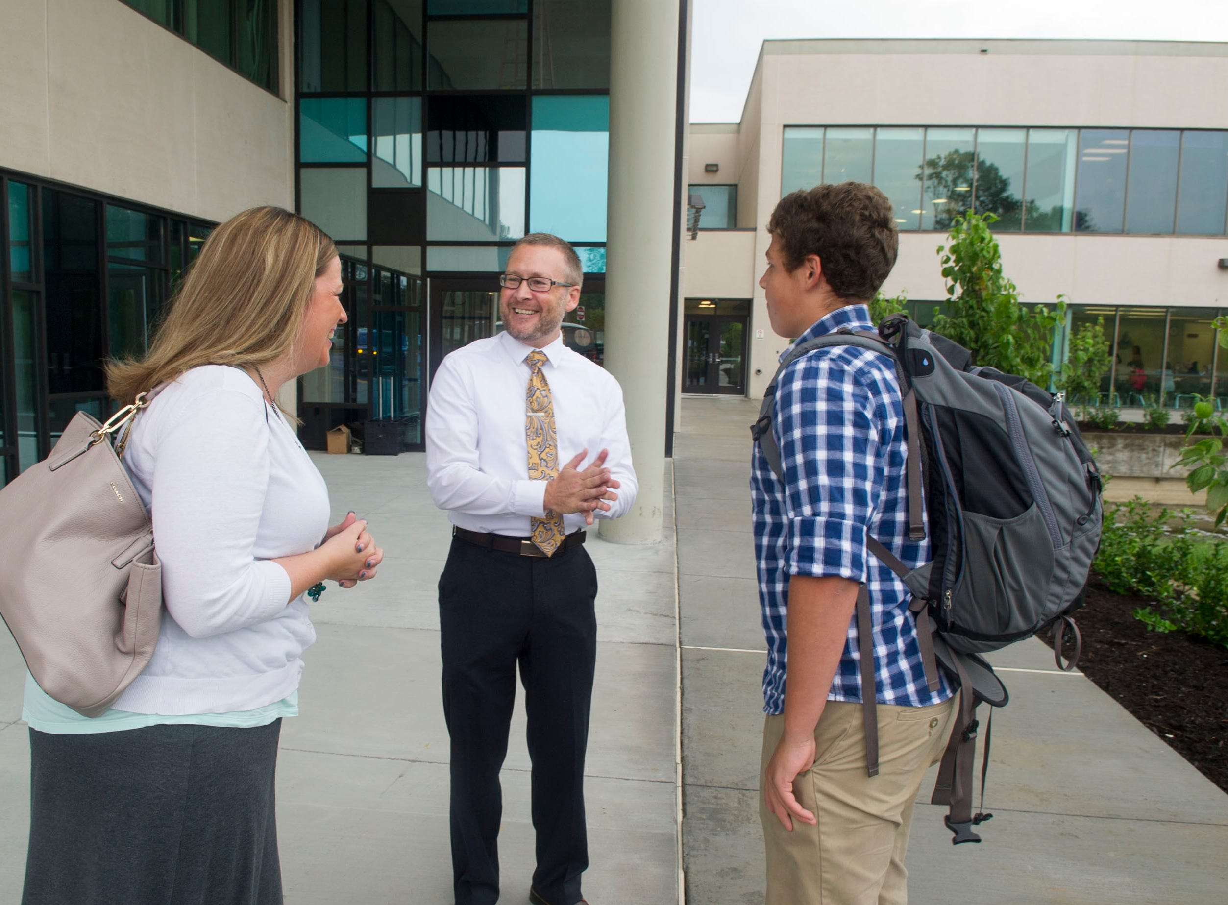 John Derek Faulconer, center, principal of the new Knox County Schools Career Magnet Academy at Pellissippi State, talks with Lea Ann Stanford, left and her son Connor Peak, before the start of orientation, Friday, August 8, 2014.  Knox County Schools opened the Career and Technical Education Magnet high school located on the Pellissippi State Community College campus at Strawberry Plains, Friday, August 8, 2014.  The opening comes on the heels of a state and national push toward increasing these type of programs for students. The new CTE magnet high school, a partnership with Pellissippi State Community College and the Knoxville Chamber, as well as academic and business leaders, will offer students courses in advanced manufacturing, sustainable living, homeland security and teacher preparation. Students were on campus for freshman orientation.  John Faulconer is the principal of the new high school.