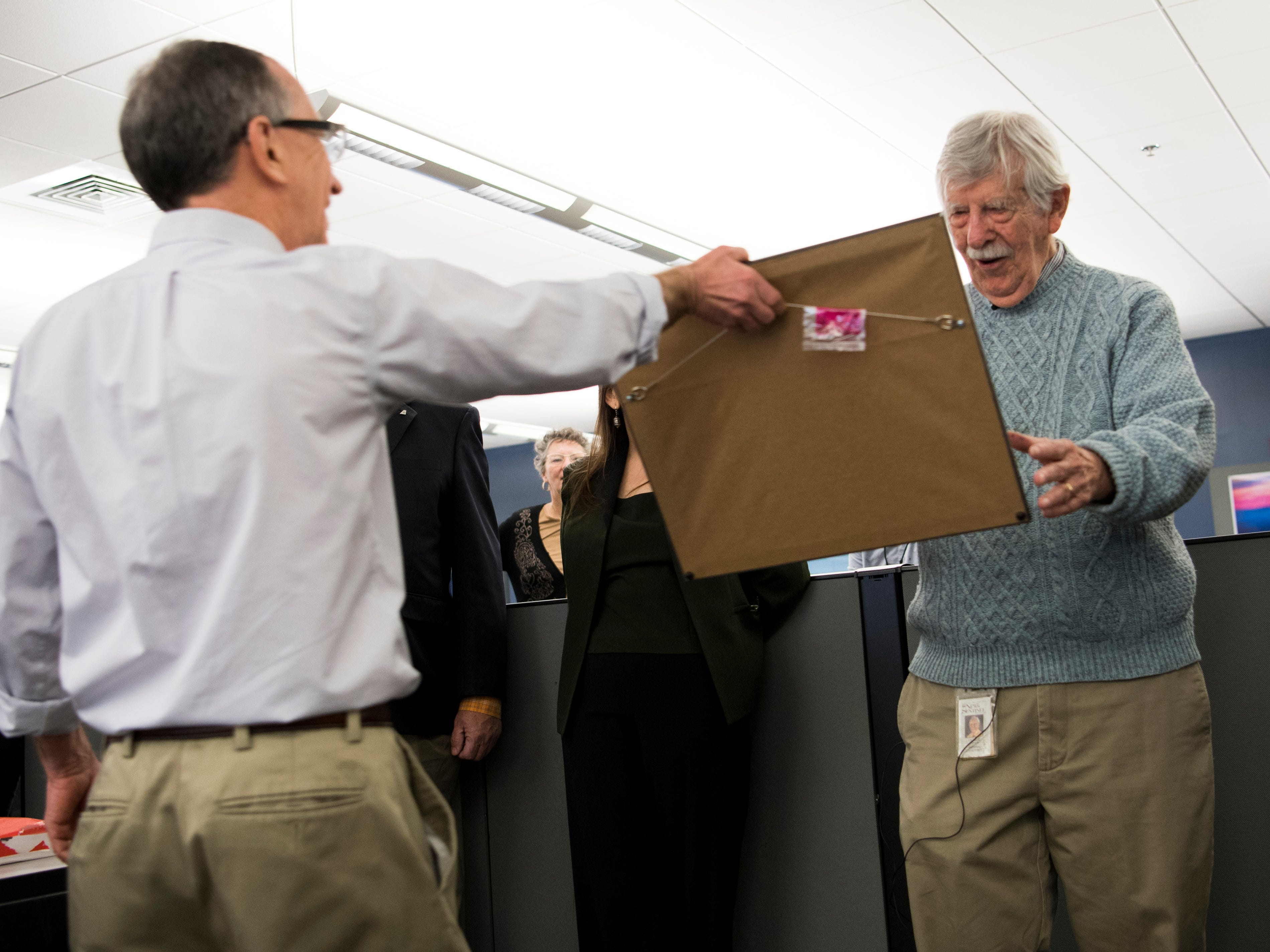News Sentinel Executive Editor Jack McElroy hands cartoonist Charlie Daniel a custom cartoon draw for Daniel during a celebration for the retirements of executive editor Jack McElroy and cartoonist Charlie Daniel in the News Sentinel newsroom on Friday, February 1, 2019.