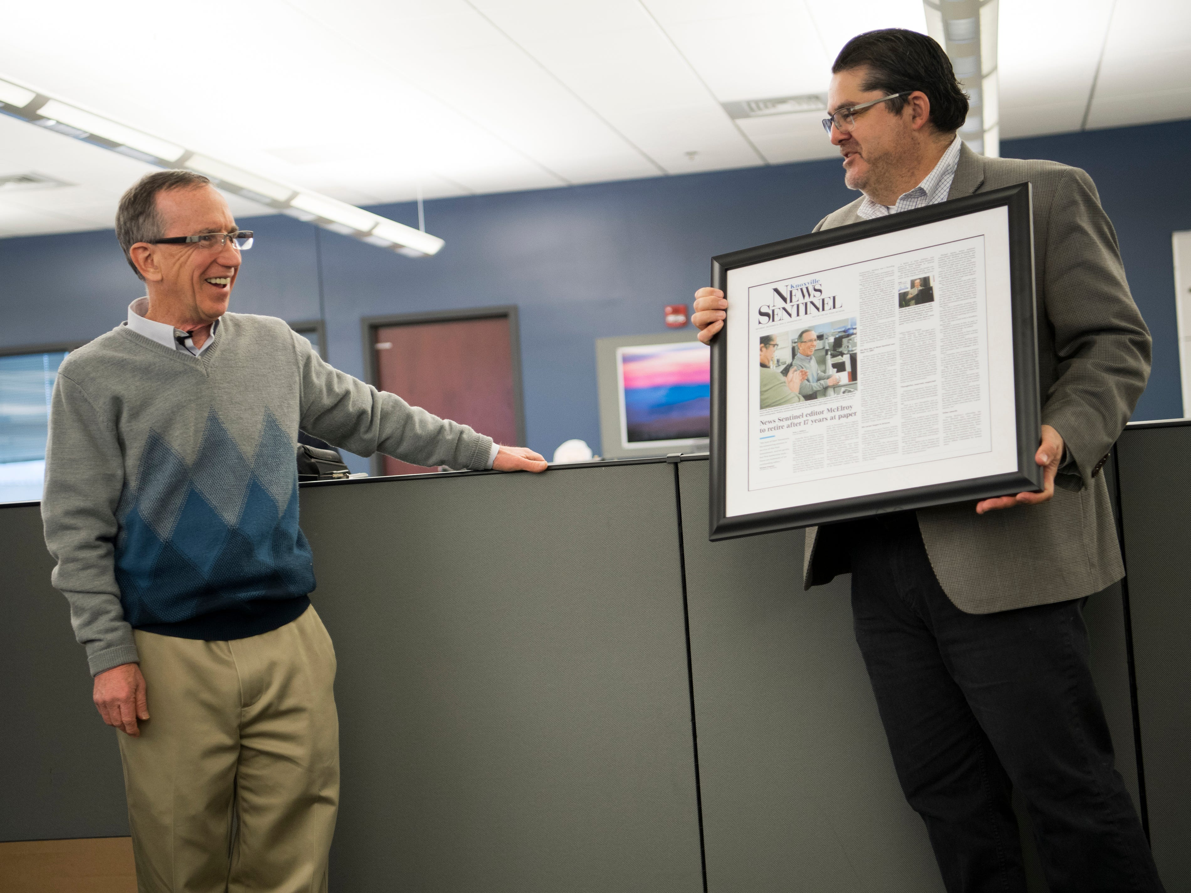 Michael Anastasi, Vice President/News for USA TODAY NETWORK Tennessee, shows executive editor Jack McElroy a framed News Sentinel front page during a celebration for the retirements of executive editor Jack McElroy and cartoonist Charlie Daniel in the News Sentinel newsroom on Friday, February 1, 2019.