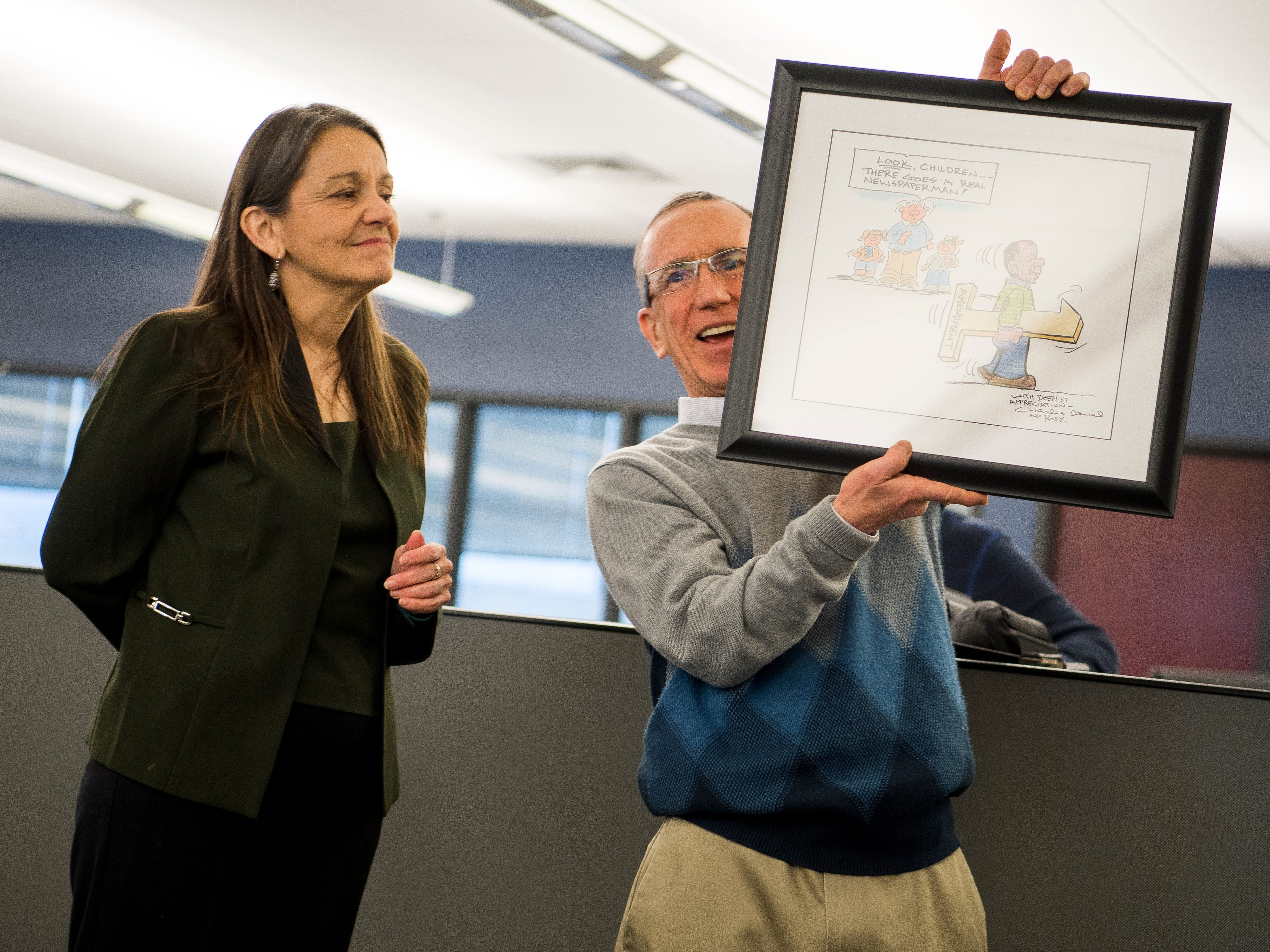 News Sentinel Executive Editor Jack McElroy shows the newsroom his custom Charlie Daniel cartoon during a celebration for the retirements of executive editor Jack McElroy and cartoonist Charlie Daniel in the News Sentinel newsroom on Friday, February 1, 2019.