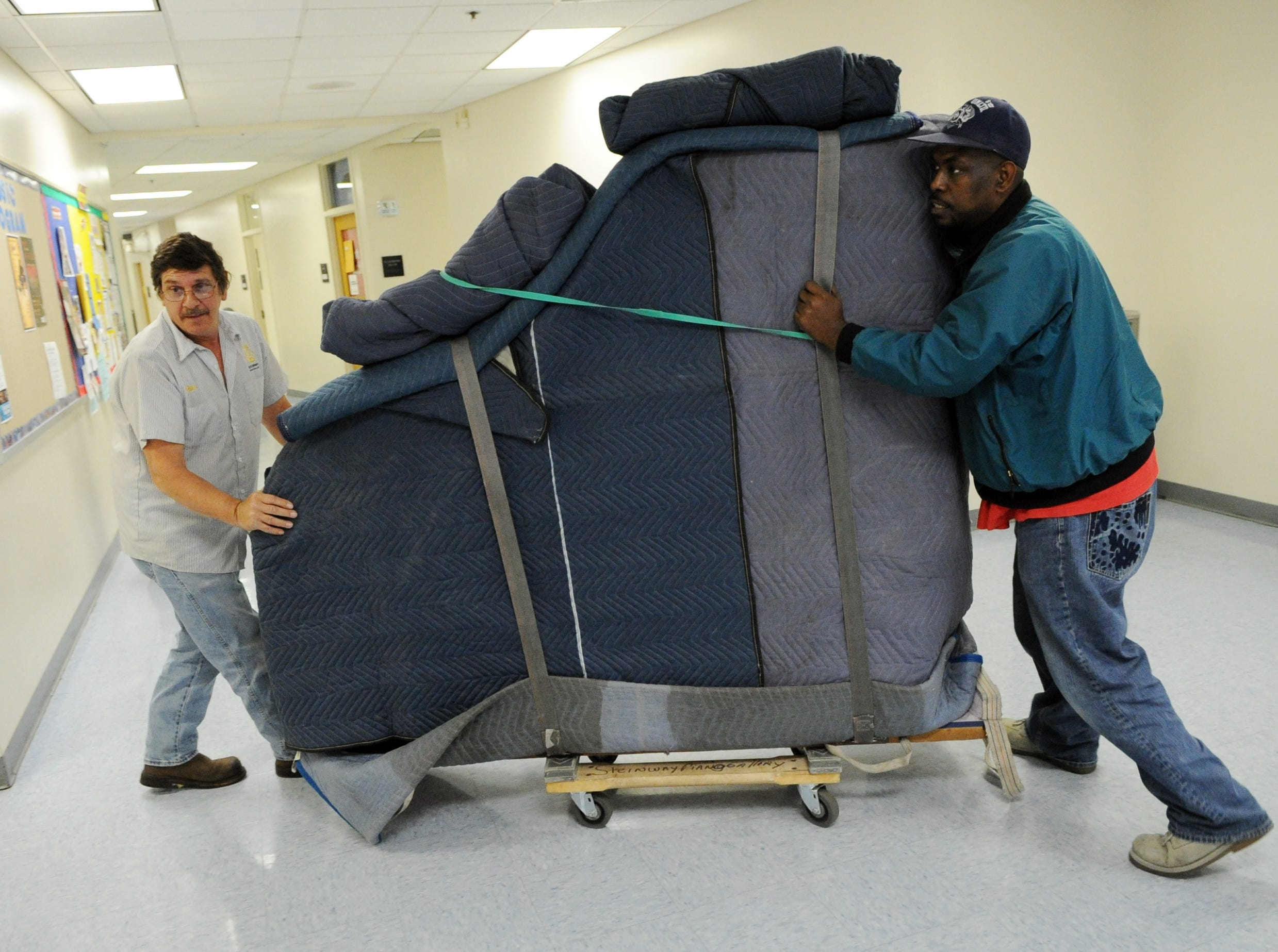 Mike Dheohary, left, and Kevin Forester, right, with the American Piano Gallery deliver a Steinway grand piano to a classroom at Pellissippi State Community College Thursday, May 5, 2011.