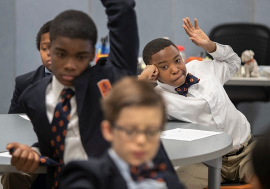Malachi Ibn-Mohammed, right, raised his hand to answer a question in class at the W.E.B. Dubois Academy. Feb. 1, 2019.