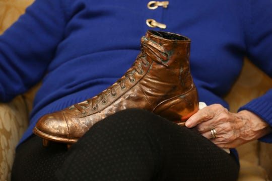 Mary Sandusky, wife of former Baltimore Colts guard Alex Sandusky, sat with one of the shoes he wore during the famed 1958 NFL championship game.  He spoke to a group about his time in the NFL and his participation in the game.