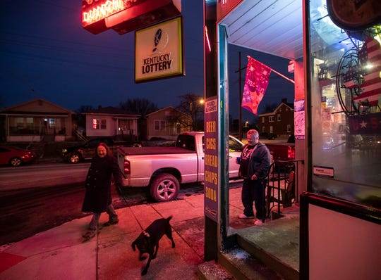 A man walks his dog along Goss Avenue while Billy Compton stands outside Hauck's on the last night the store was open. Jan. 31, 2019.