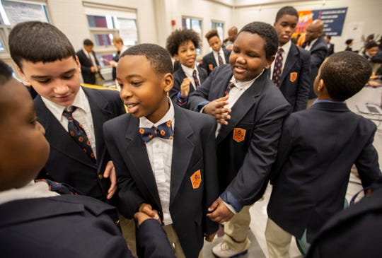 "Malachi Ibn-Mohammed, center, shakes hands with another classmate during the ""Sharing Love"" segment, held during morning announcements at the W.E.B. DuBois Academy. Feb. 1, 2019"