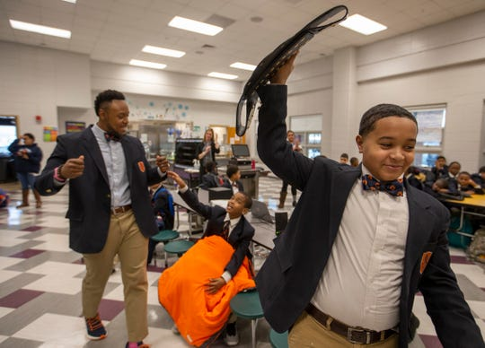 Kaden Baker holds the Champion's Belt in the air after accepting it from W.E.B. Dubois Academy principal Robert Gunn Jr. Baker was awarded the belt for his recent MAP test scores. Feb. 1, 2019