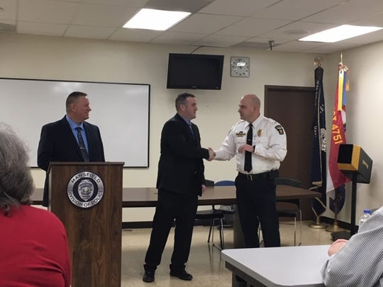 New Mansfield police Officer Evan Hout, 26, of Mansfield, center, was sworn in Friday at the Mansfield Police Department. At left is Mansfield police Chief Ken Coontz. At right, Assistant police Chief Keith Porch.