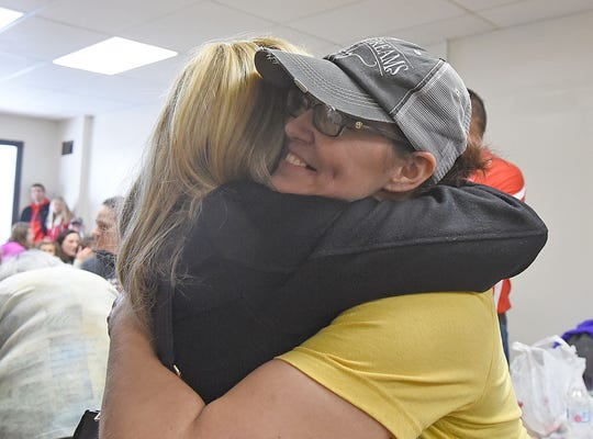 Jessica Carver accepts hugs from well-wishers during the ribbon cutting ceremony for her new bakery Sweet Dreams in Shelby.