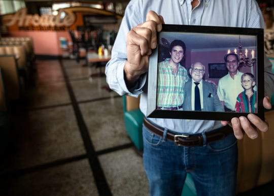 Harry Zepatos holds a family photo at Arcade Restaurant, which continues to be a family-run business.
