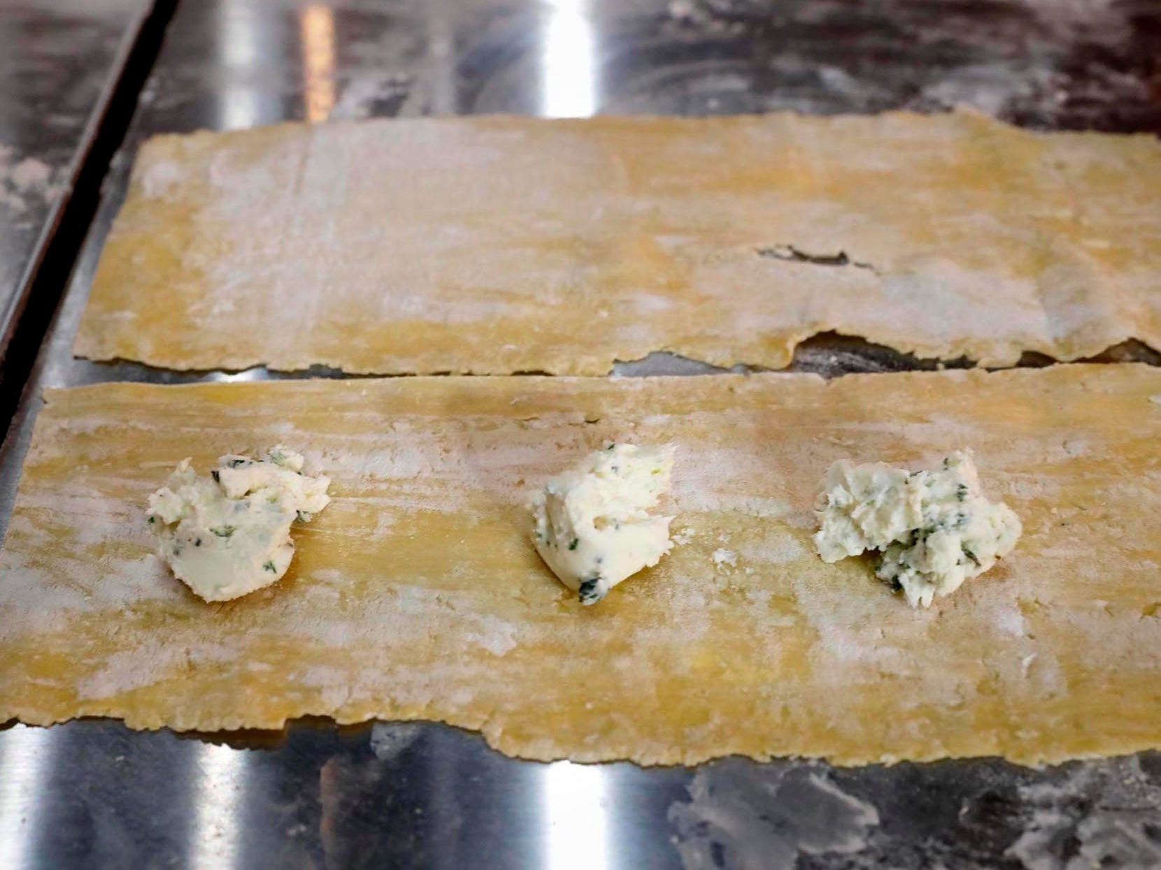 Herbs added to ricotta cheese are spooned onto pasta sheets to become individual ravioli.