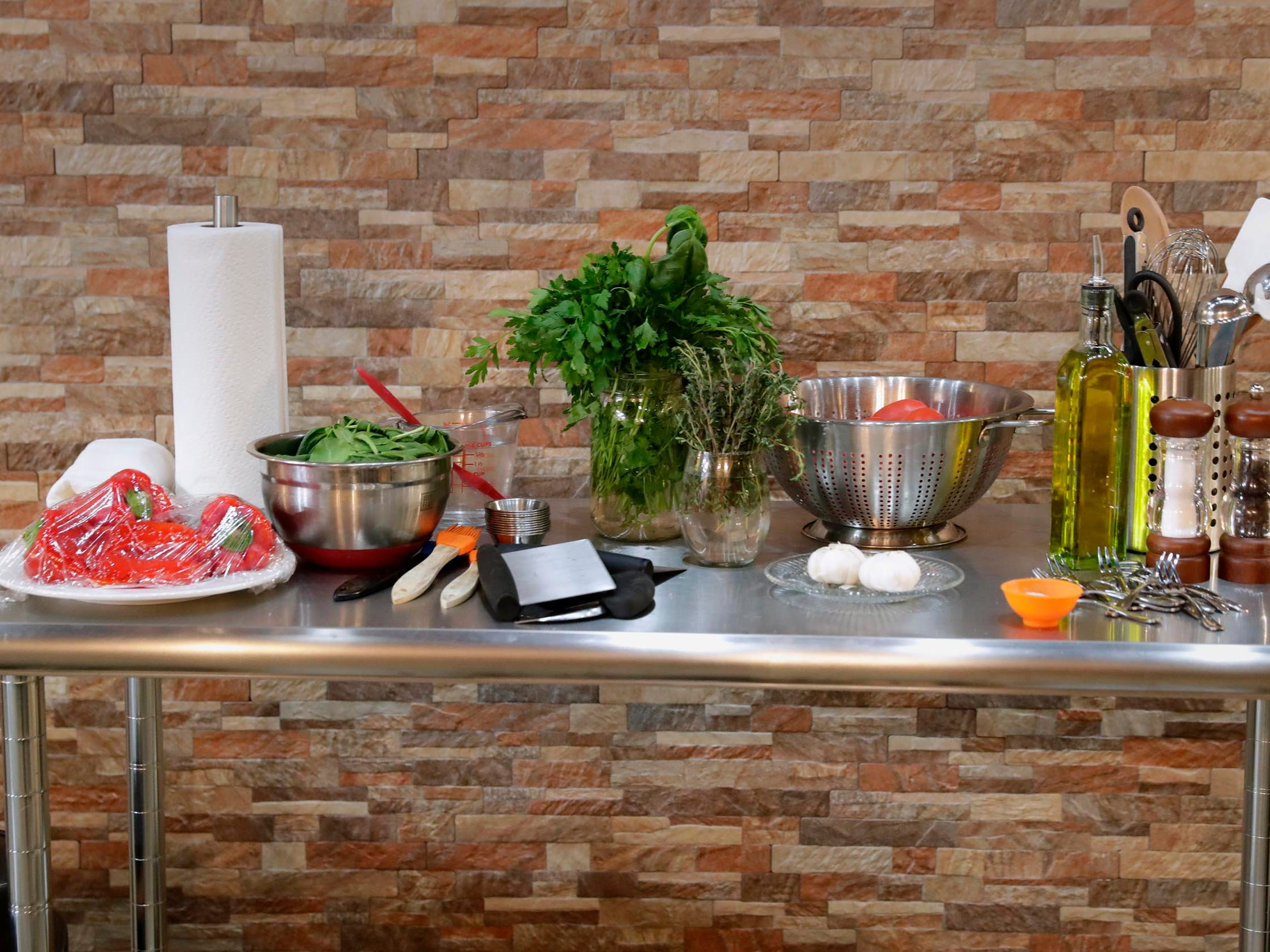 The instructor's station stands ready with roasted red peppers, herbs, spinach, tomatoes, eggs and more.
