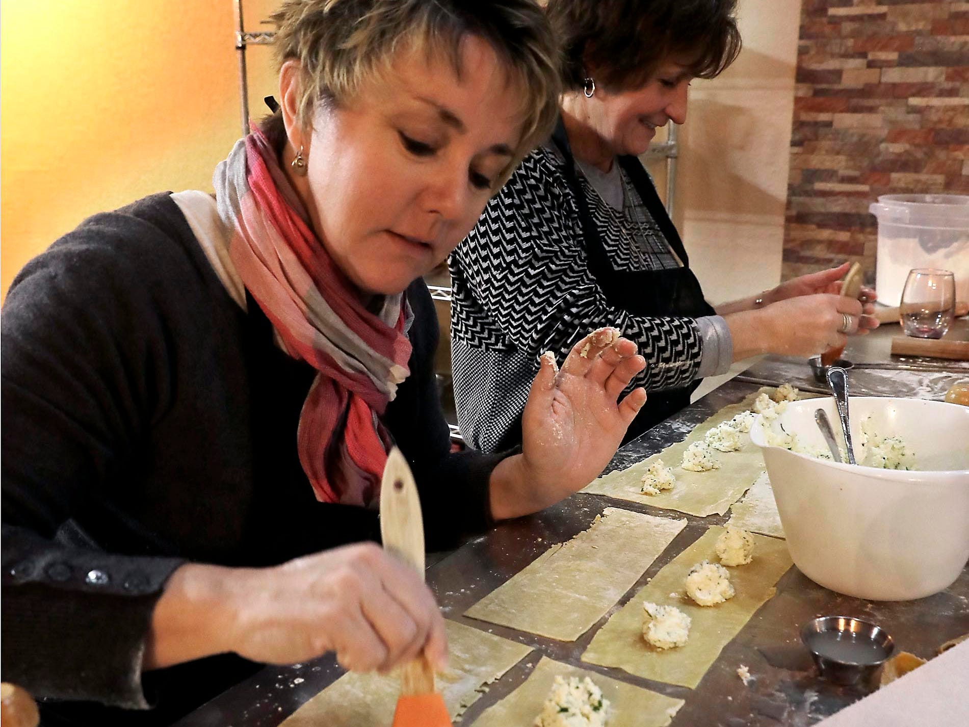 Lori Cieslik brushes water on ravioli dough before placing a second layer of dough on top.