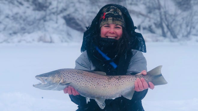 Hannah Stonehouse Hudson holds a brown trout she caught while ice fishing on Lake Superior near Bayfield.