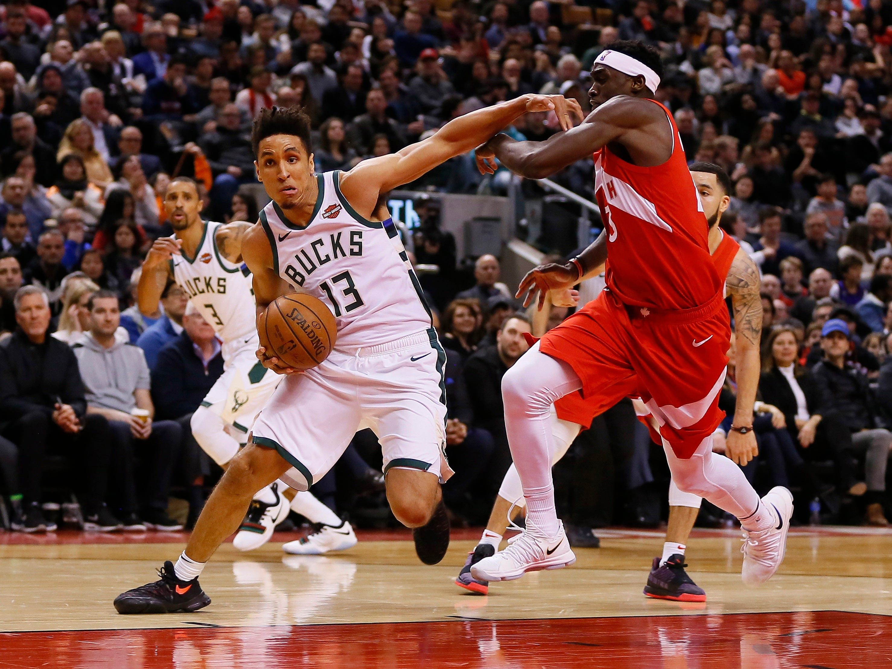 Bucks guard Malcolm Brogdon gets past Raptors forward Pascal Siakam as he heads to the basket during second-half action on Thursday night.