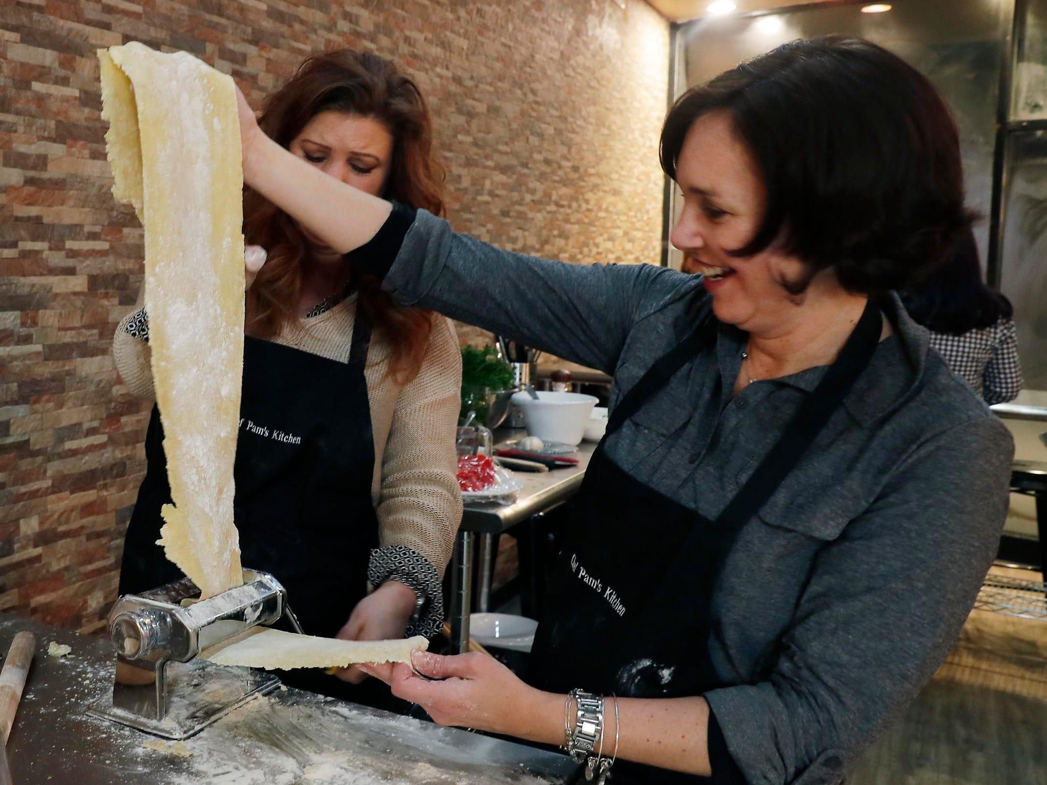 Chris Liedtke (left) and Beth Zeiler work together to run ravioli dough through a pasta press.