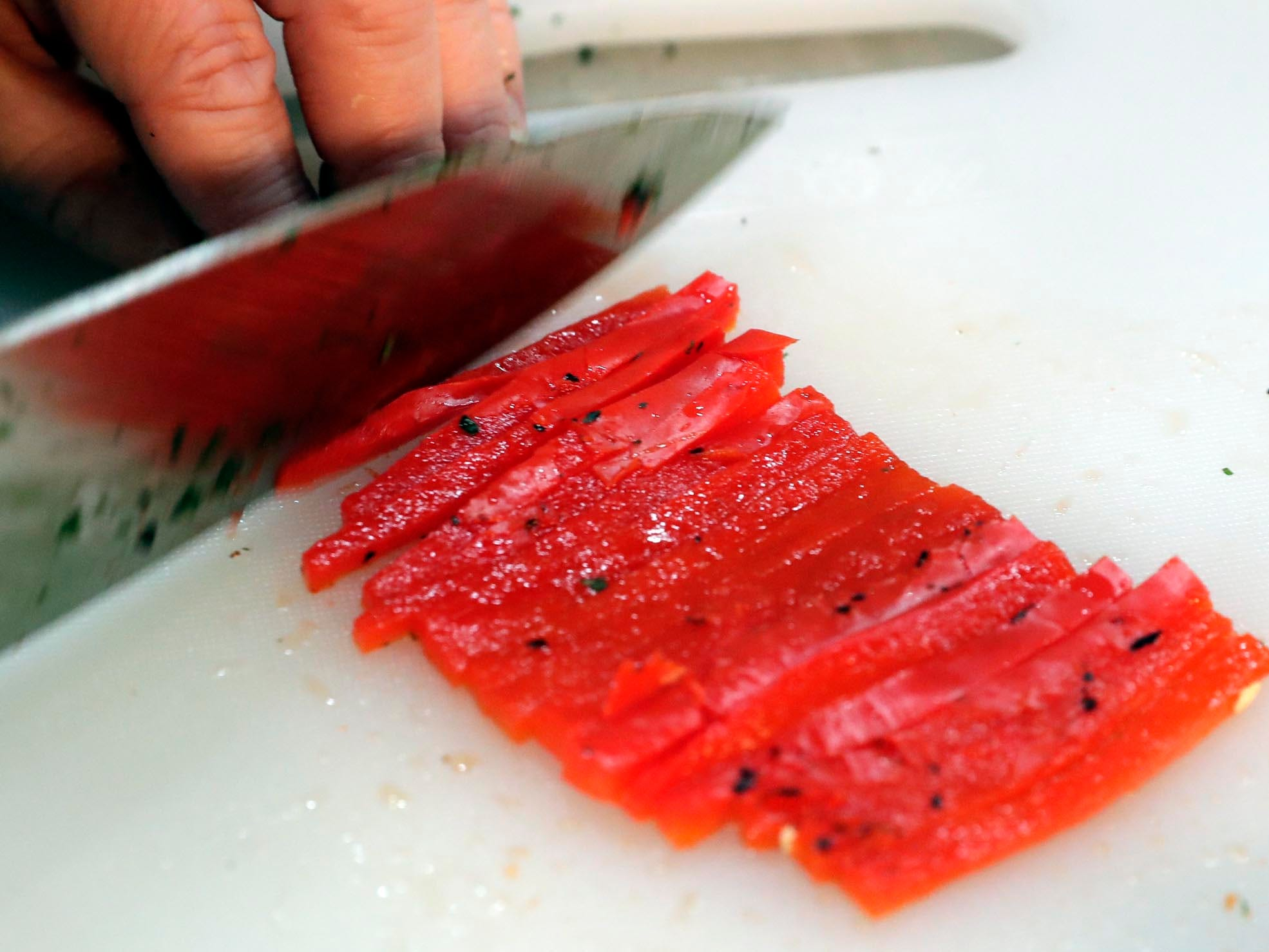 Roasted red peppers are sliced matchstick thin for one of the ravioli sauces.