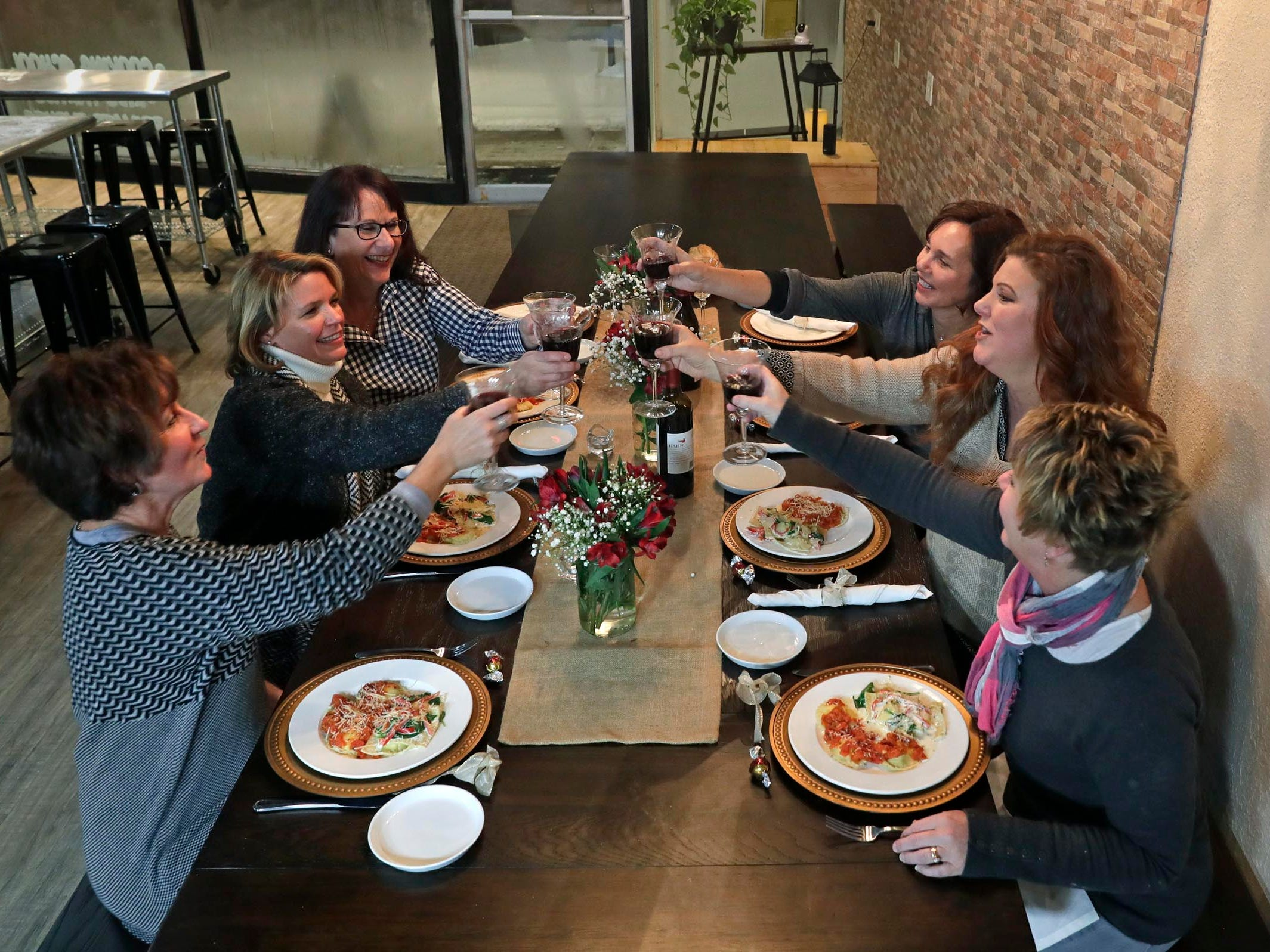 Students share a toast after a class at Chef Pam's Kitchen in Waukesha.