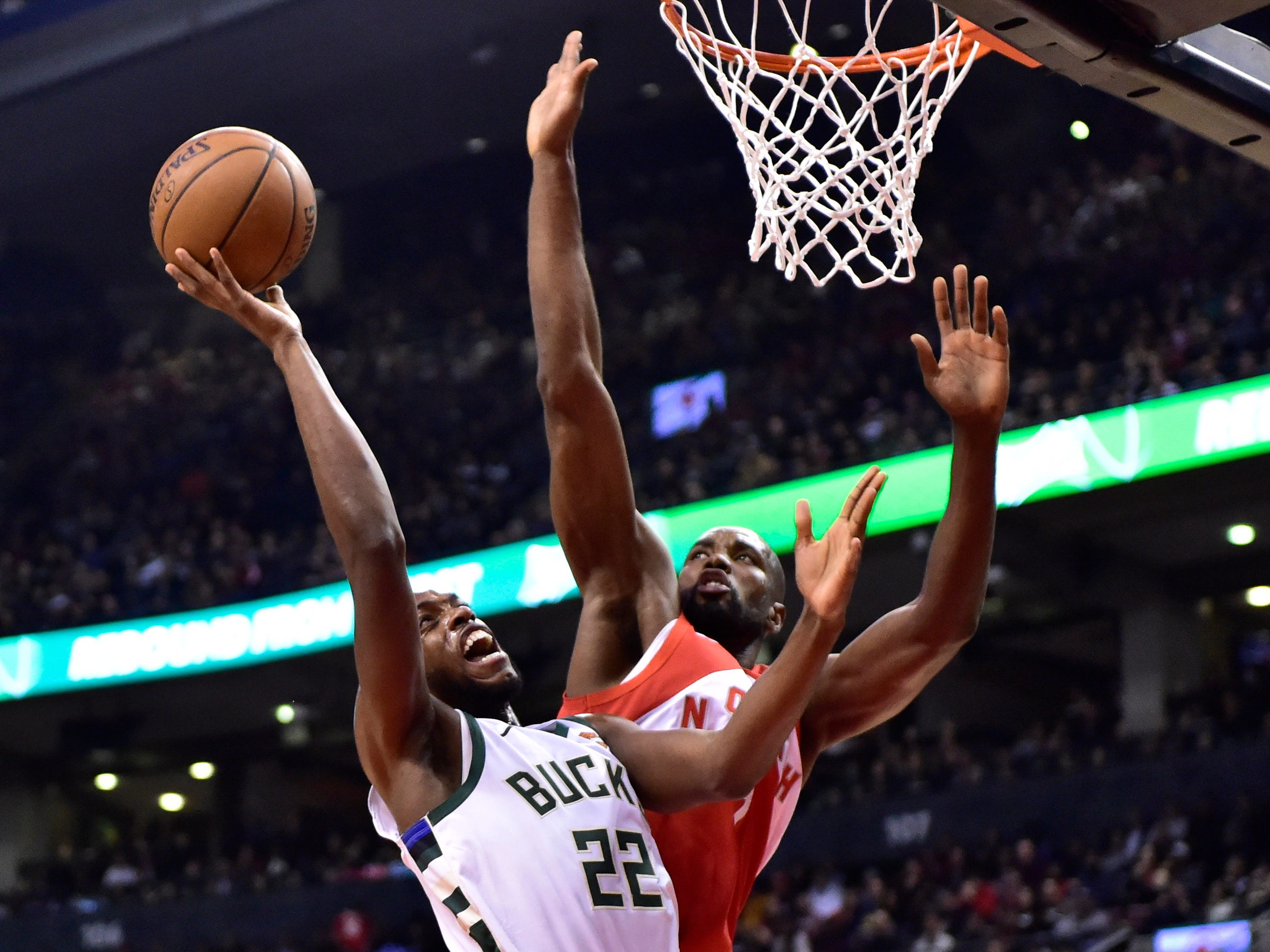 Khris Middleton,  who was named as an All-Star Game reserve before the Bucks' game in Toronto, goes up a shot down low against Raptors big man Serge Ibaka during the first half Thursday.