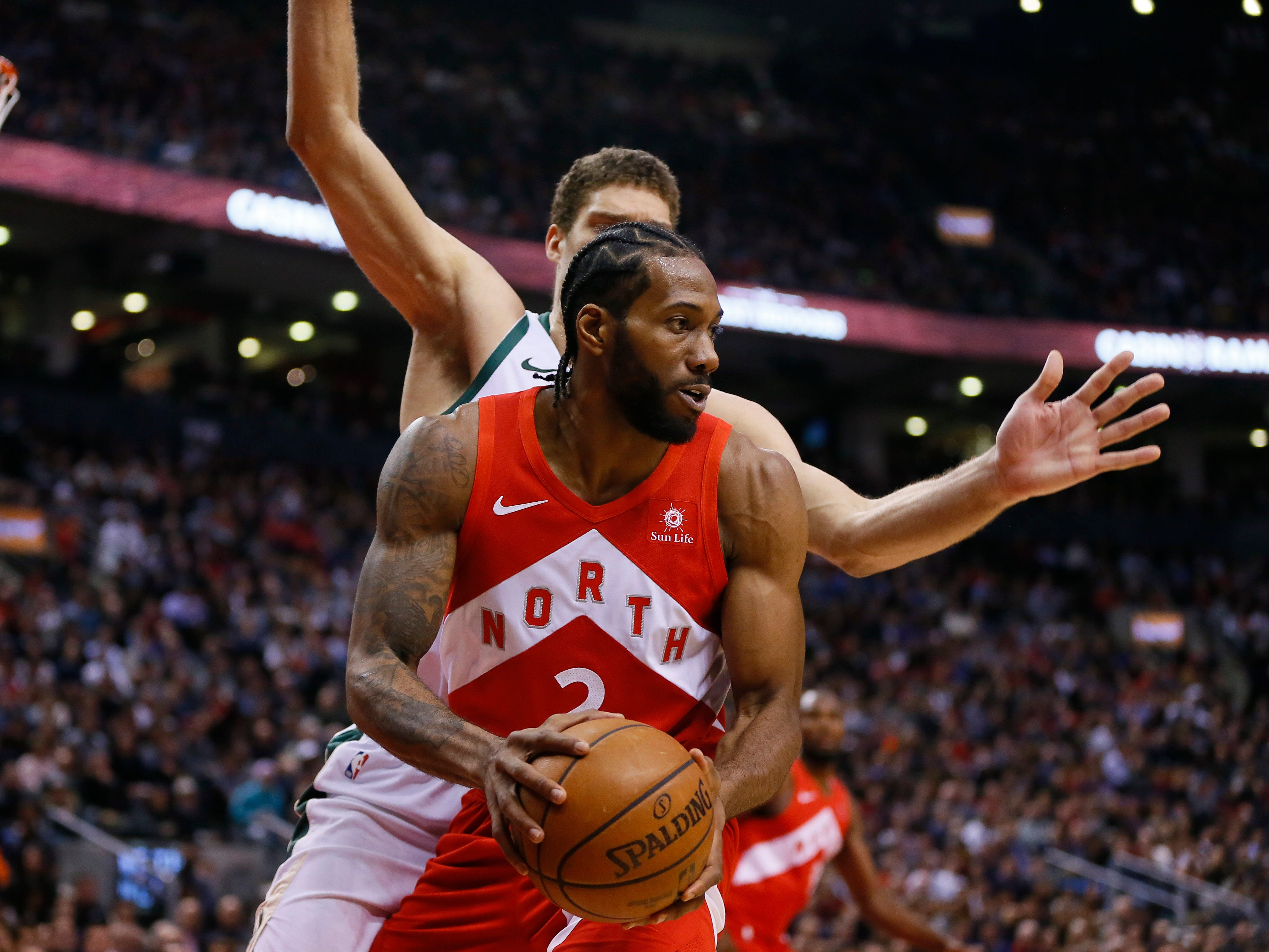 Raptors forward Kawhi Leonard ponders his next move as he's guarded by Bucks center Brook Lopez in the first half Thursday night.