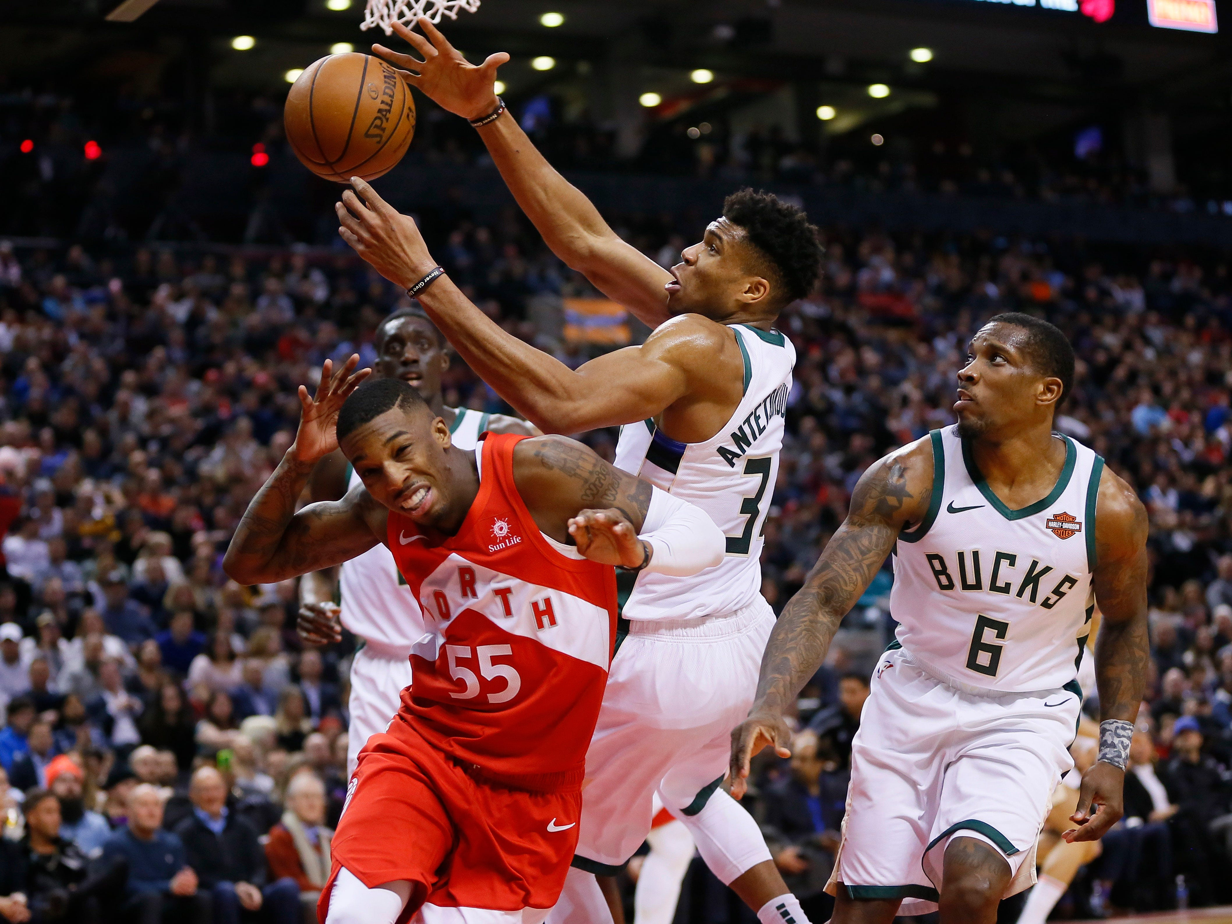 Bucks forward Giannis Antetokounmpo takes a rebound away from Raptors guard Delon Wright as Eric Bledsoe  looks on during the first half Thursday.