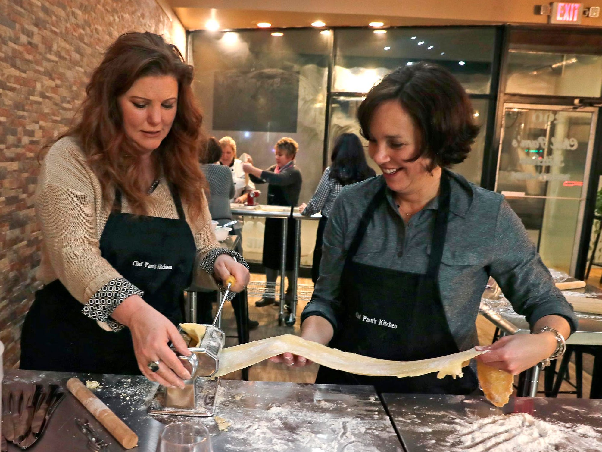 The pasta dough gets longer and thinner with each pass through the machine, as Chris Liedtke (left) and Beth Zeiler discovered.