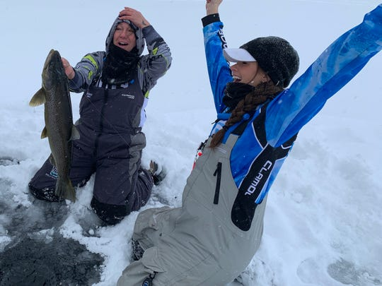 Shelly Holland lands a brown trout while Shantel Wittstruck celebrates the catch during a January 2019 ice fishing outing on Lake Superior as part of the Women Ice Angler Project.