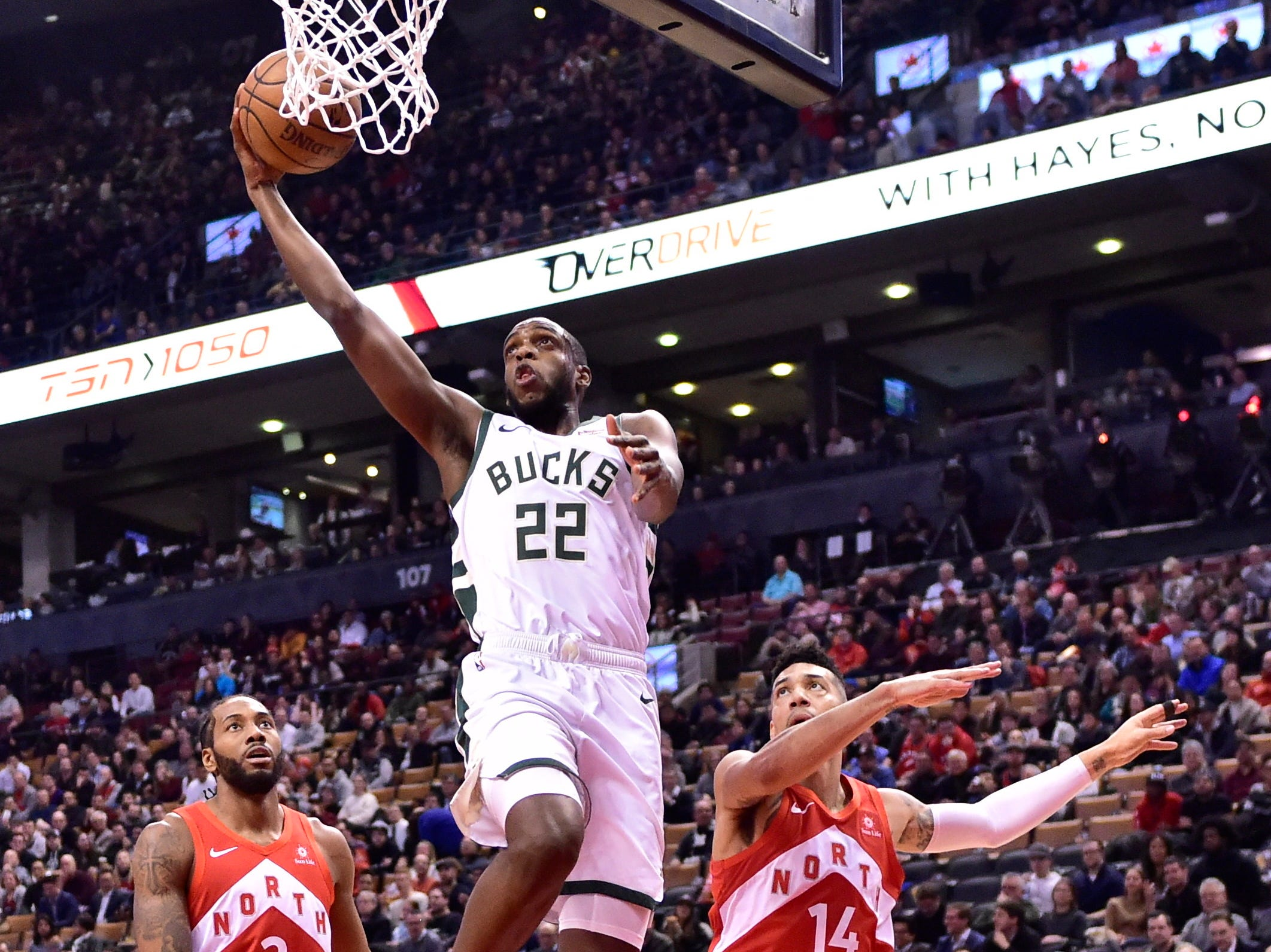 Bucks forward Khris Middleton gets between Kawhi Leonard (2) and Danny Green of the Raptors for a dunk during first-half action Thursday night.
