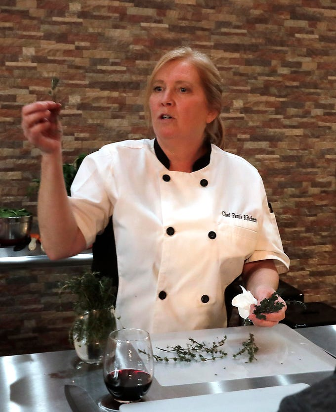 Pam Dennis shows students how to remove fresh thyme leaves from the stems.