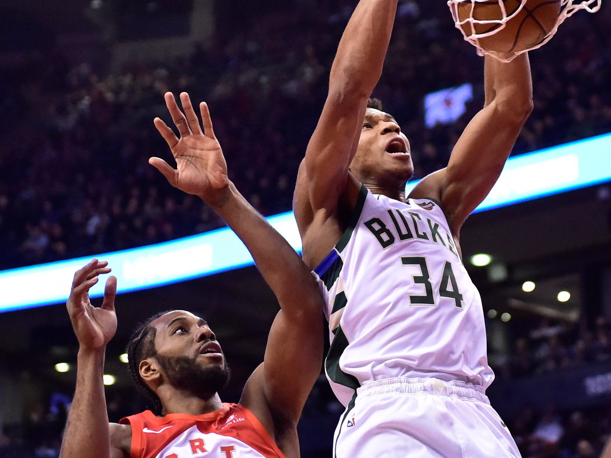 Bucks forward Giannis Antetokounmpo powers home a two-handed dunk against fellow all-star starter Kawhi Leonard of the Raptors during the first-half Thursday night in Toronto.