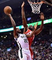 Milwaukee Bucks forward Khris Middleton and Toronto Raptors center Serge Ibaka battle under the basket during the first half in Toronto. Middleton had 18 points.