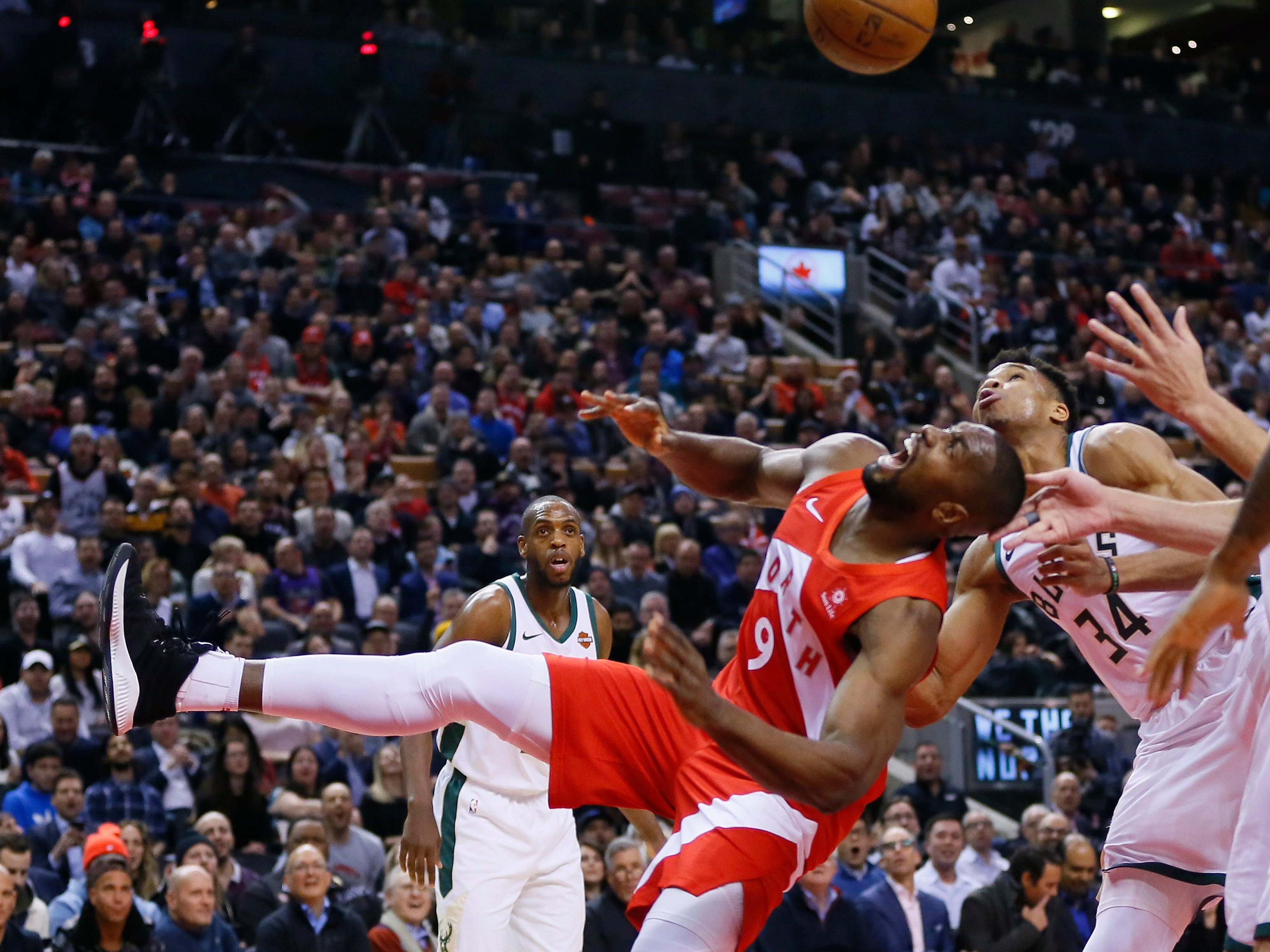 Raptors forward Serge Ibaka and Bucks forward Giannis Antetokounmpo battle for a rebound during the first half Thursday night.