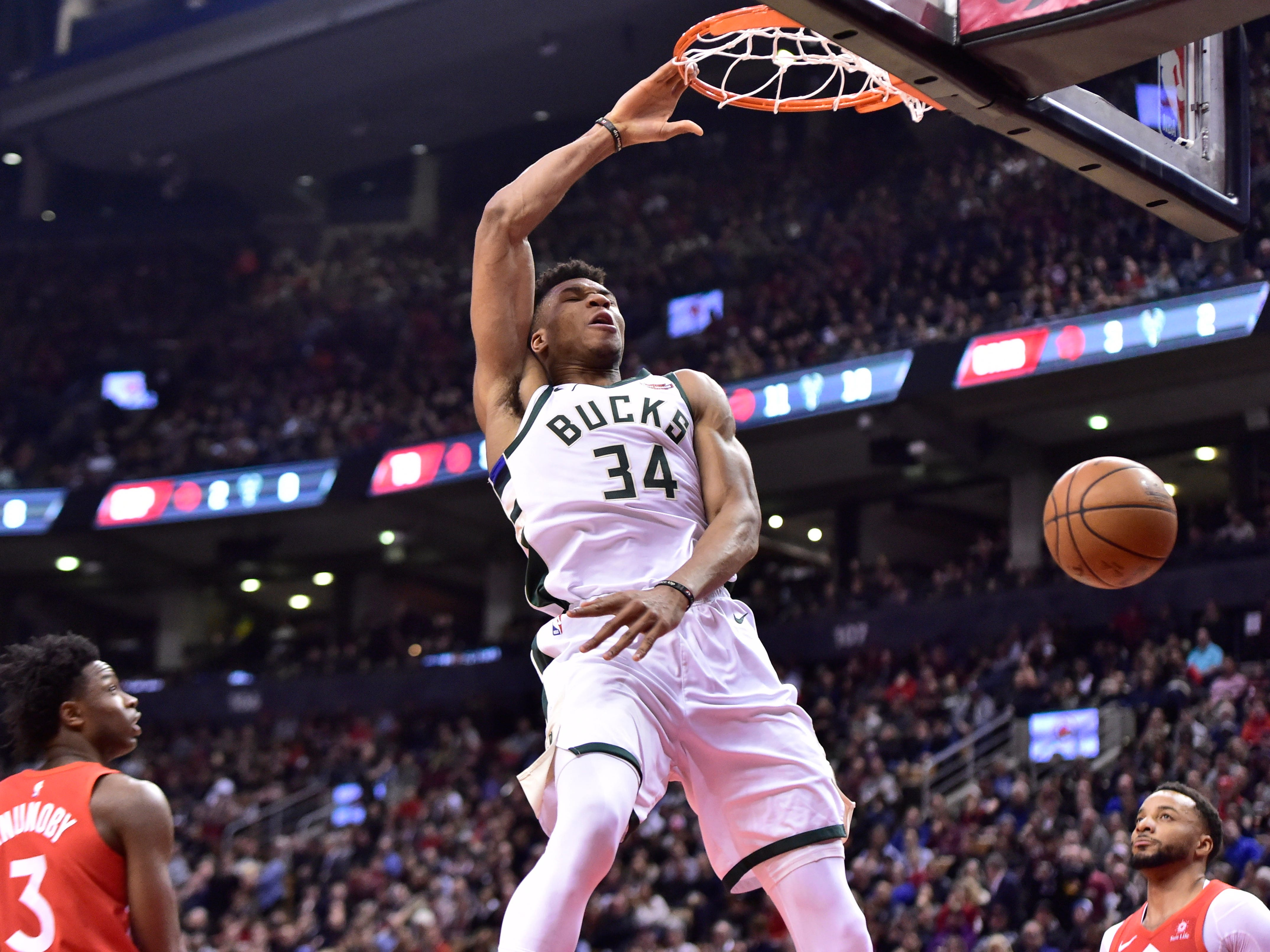 OG Anunoby (left) and Norman Powell of the Raptors helplessly watch as Giannis Antetokounmpo of the Bucks slams home two points during the first half Thursday night.