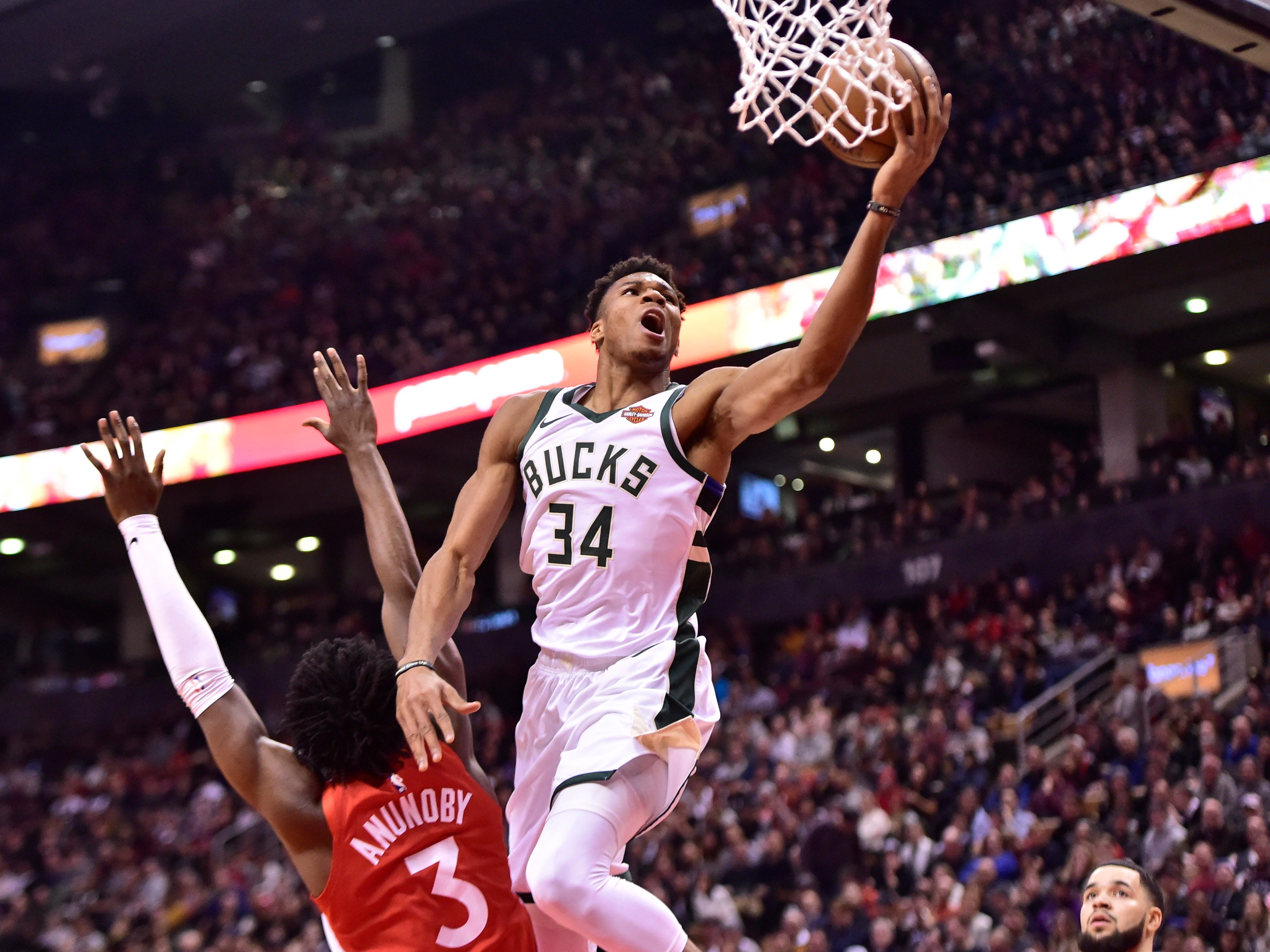 Bucks forward Giannis Antetokounmpo throws up a finger-roll after getting around Raptors forward OG Anunoby during first half Thursday night.