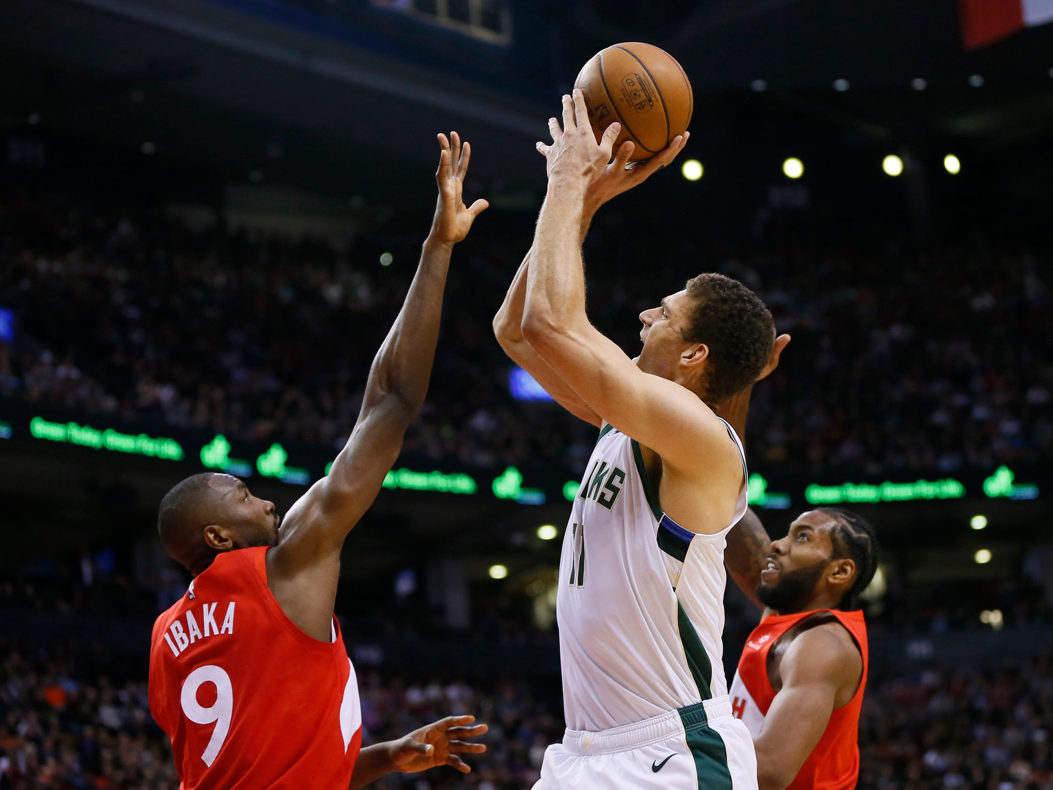 Bucks center Brook Lopez puts up and hits a big shot late in the game over Raptors forward Serge Ibaka on Thursday night.